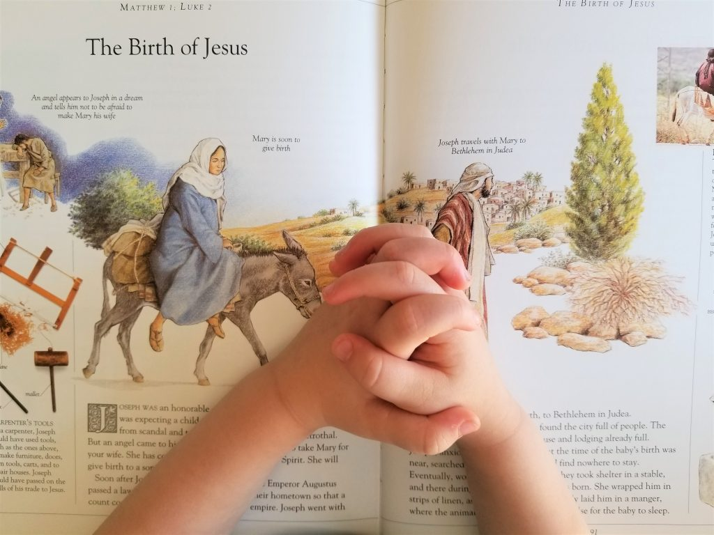 child prayer hand on bible